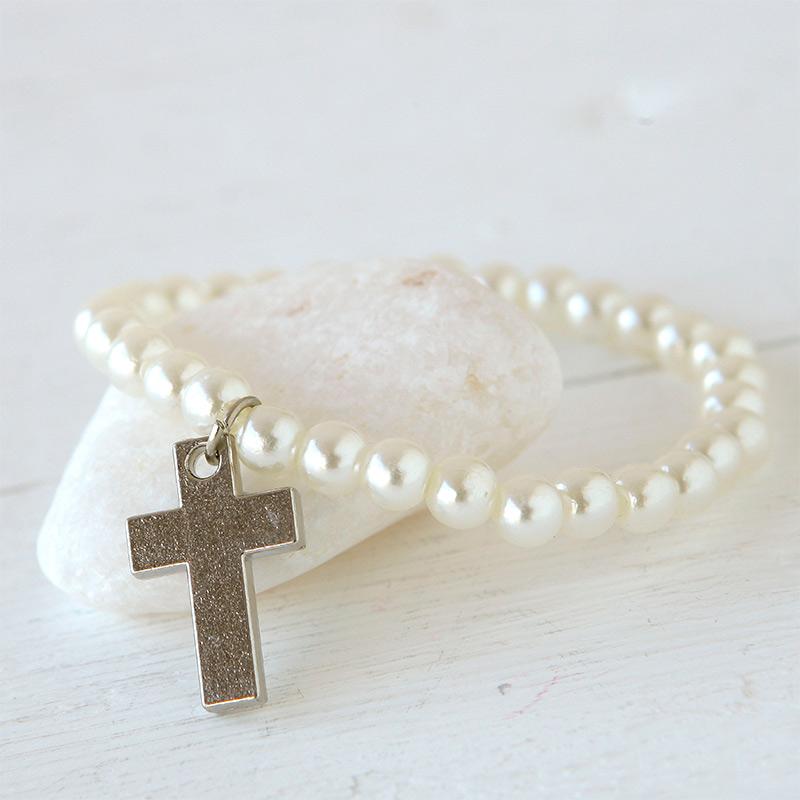 Pulsera de perlas con abalorio de cruz religiosa.
